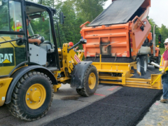 Road Widener loader attachment laying asphalt